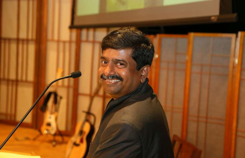 Rev. Abhi Janamanchi turning his head and smiling at the camera in front of the Cedar Lane pulpit
