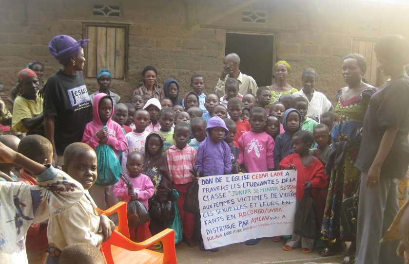 """This photo represents a seedling that changed many lives. The sign reads, in part: """"[Clothing] donation of Cedar Lane Church, through the students of the 'Junior Seminar' class, session 2, for survivors of gender-based violence and their children."""""""