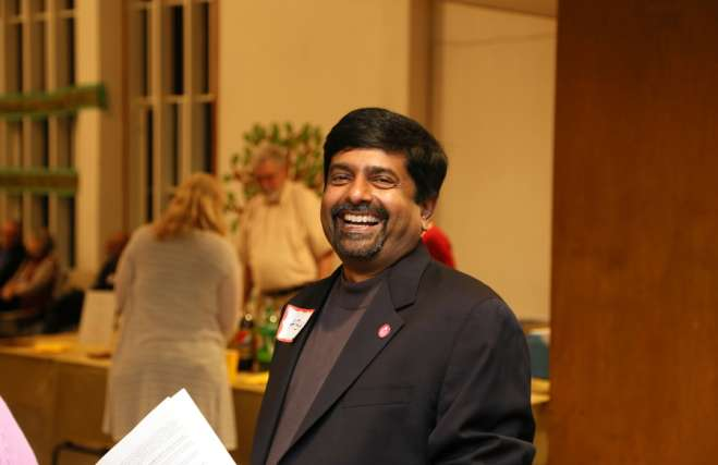 photo of rev. Abhi Janamanchi at the 2017 fall auction in the Cedar Lane Sanctuary smiling and looking at the camera