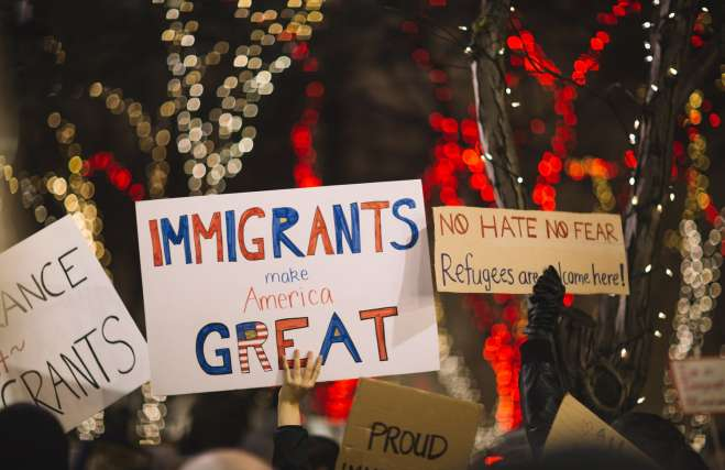 "photo of a rally for immigrants with people holding signs, the one in the center says ""Immigrants Make America Great"""