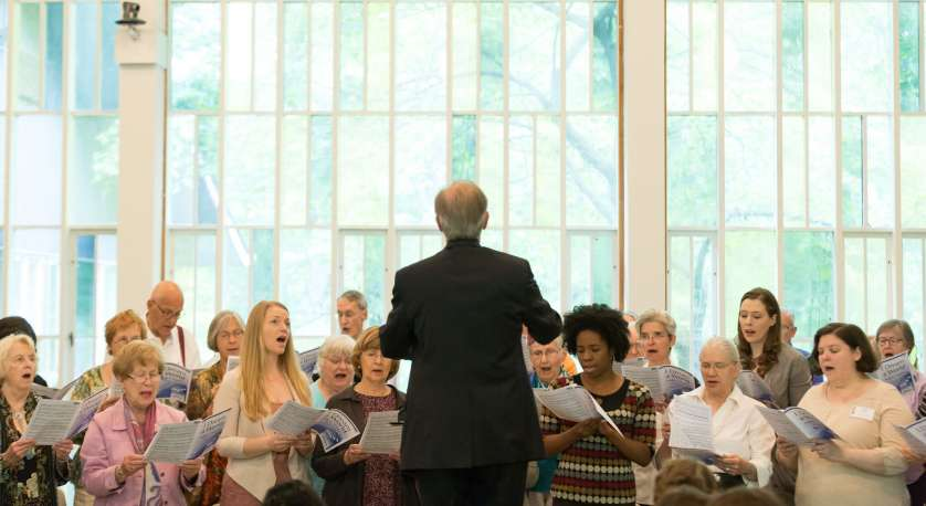 photo of Music Directory Henry Sgreeci directing the Adult Choir at Cedar Lane with stained glass windows in background