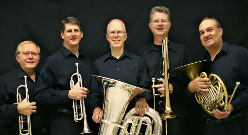 photo of the National Brass quintet with their instruments standing and posing for professional photo in black shirts