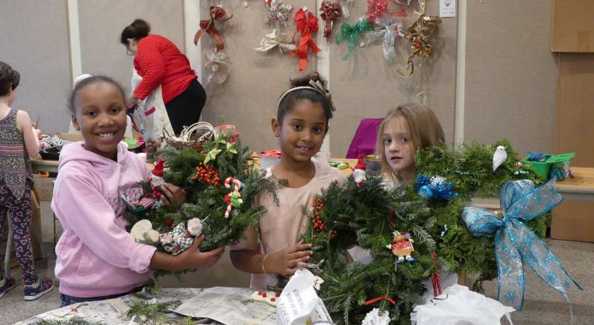 young girls with wreaths they made during Holiday Craft Day