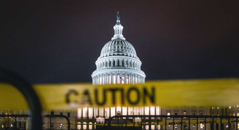 "photo of the capitol building at night with a big ""caution"" tape in front of it"
