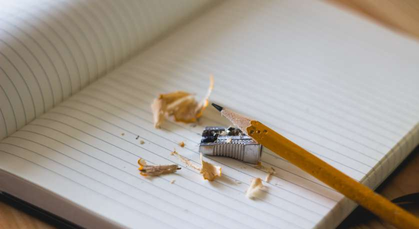 pencil with a sharpener and shavings on a blank pad of paper