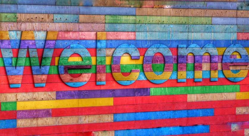 welcome written in colors of the rainbow against a rainbow background