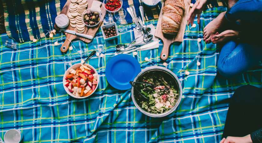 beautiful picnic spread on a bright teal checkered blanket