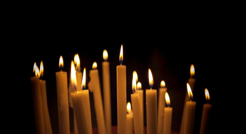 light tall candles close together in a black background