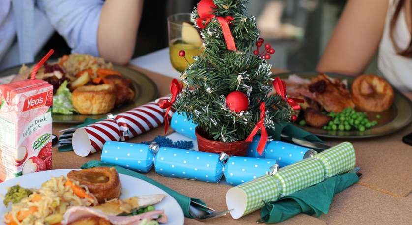 people gathered around eating Christmas Diner with some holiday decor on the table
