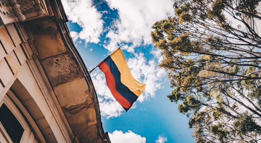 Colombian flag against a blue sky with tree and building also in frame