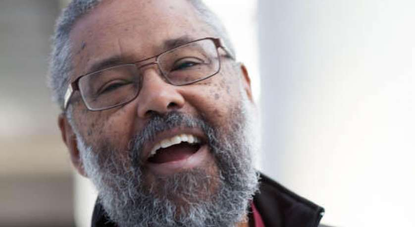 headshot of Rev. Mark Morrison-Reed smiling and laughing with his mouth open, in a collared shirt, sweater, and coat
