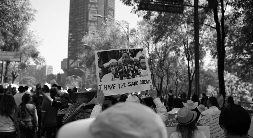 "photo of a rally with someone holding up a sign that says ""I have the same dream"" with a photo of Rev. Dr. Martin Luther King, Jr"