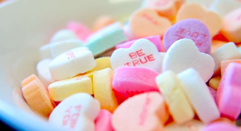 bunch of heart-shaped Valentine's Day candies in a bowl