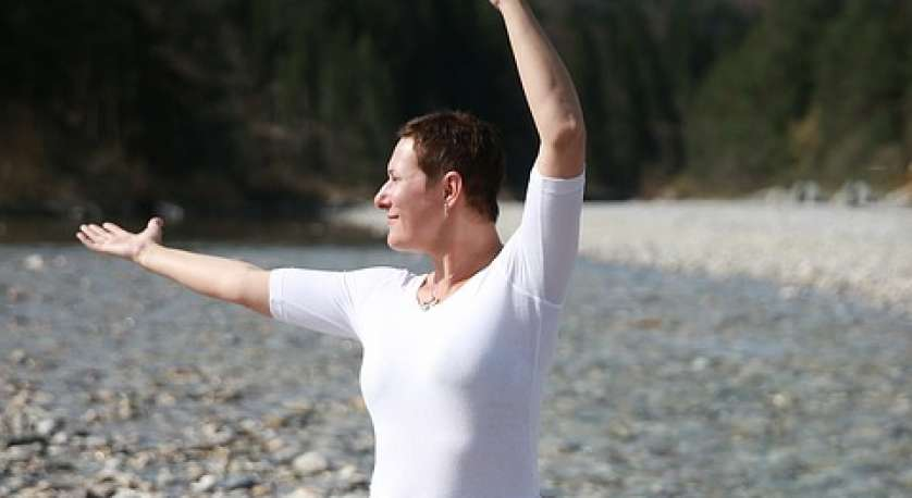 a middle aged woman standing and doing tai chi on a rocky beach during the day