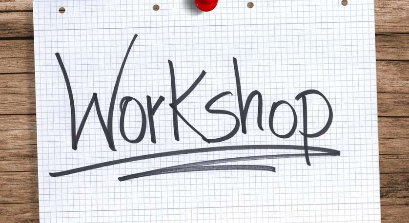 """a piece of paper tacked to a wood wall with """"Workshop"""" written across it in large letters"""
