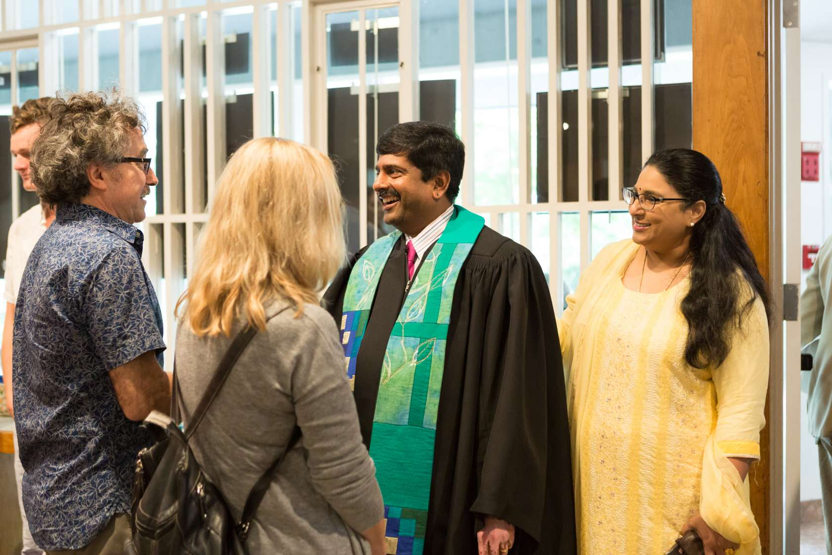 photo of Rev. Abhi and his wife in the welcoming line to greet congregants after worship on a Sunday