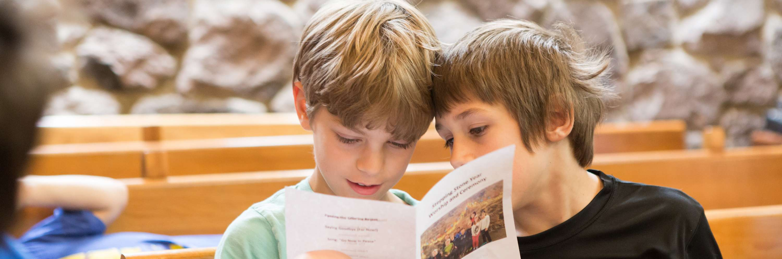 Two boys sitting in a pew reading a text