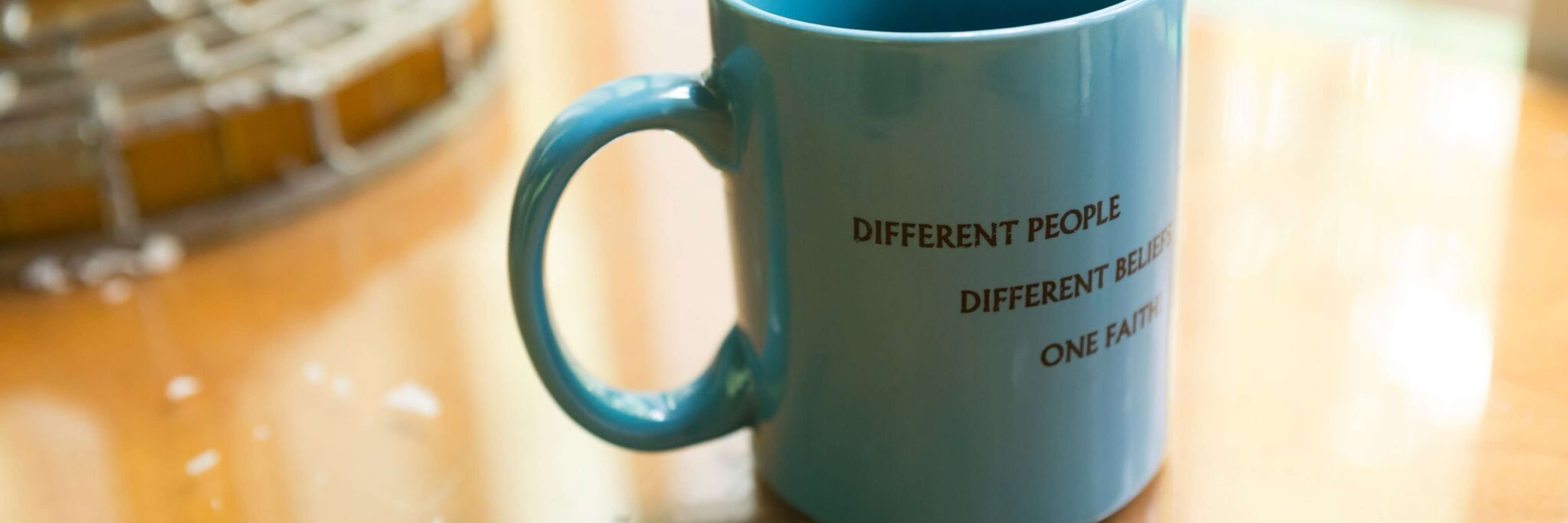 "coffee mug on a table that says ""different people, different beliefs, one faith"""
