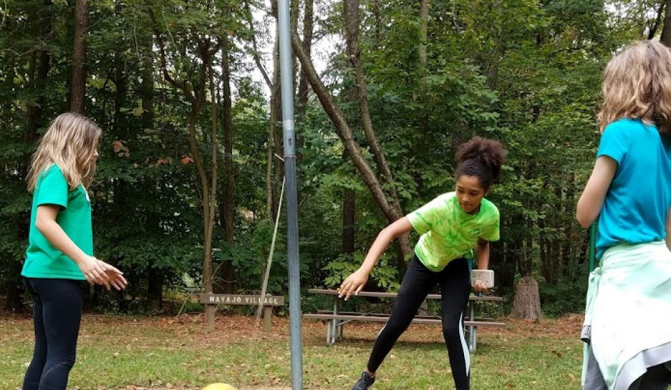 three female youth playing tether ball outside at Camp Tockwogh