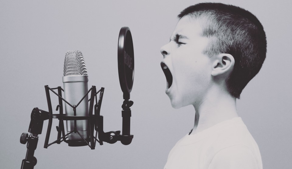 young boy singing into a professional microphone, picture in black and white