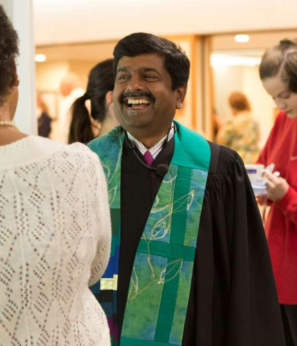 Rev. Abhi and members after worship having coffee and laughing together standing up
