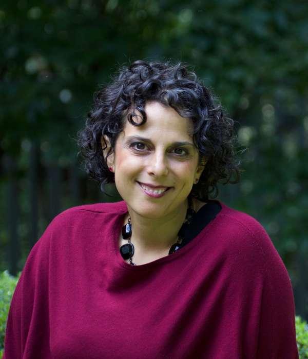 headshot in Cedar Lane courtyard of Reverend Katie Romano Griffin in burgundy sweater