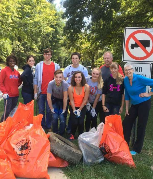 rock creek clean-up from last year with lots of adults and youth holding bags full of recycling and trash from the clean-up