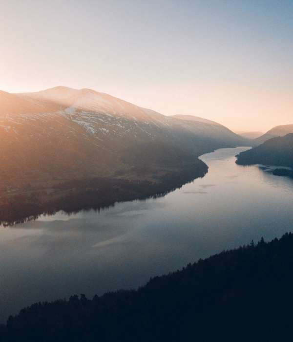 a distant view from a river with the sun shining down into the water, view is from a mountain top