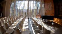 view of the stained glass windows in the sanctuary with rows of empty chairs