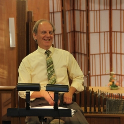 Dr. Henry Sgrecci laughing in the Choir Loft in front of a music stand